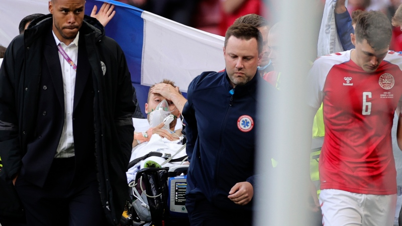 Paramedics using a stretcher to take out of the pitch Denmark's Christian Eriksen after he collapsed during the Euro 2020 soccer championship group B match between Denmark and Finland at Parken stadium in Copenhagen, Denmark, Saturday, June 12, 2021. (Friedemann Vogel/Pool via AP)