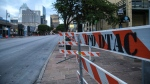Road block barriers sit on the sidewalk on 6th Street after an early morning shooting on Saturday, June 12, 2021 in downtown Austin, Texas. Authorities say someone opened fire on the busy entertainment district wounding several people before getting away. (Aaron Martinez/Austin American-Statesman via AP)