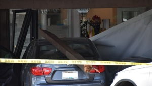Images from the scene show a grey Hyundai sedan lodged inside the bank, a wooden column from the building's covered sidewalk severed and resting atop the vehicle's back windshield. (CTV)