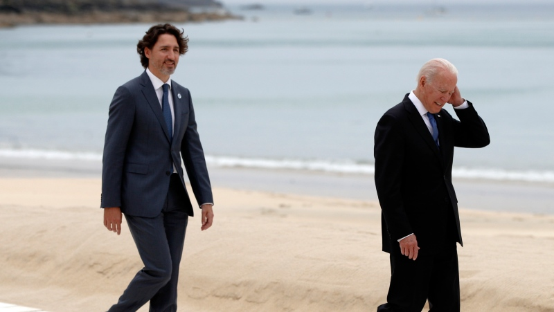 U.S. President Joe Biden, right, and Canadian Prime Minister Justin Trudeau walk on the boardwalk during arrivals for the G7 meeting at the Carbis Bay Hotel in Carbis Bay, St. Ives, Cornwall, England, Friday, June 11, 2021. (Phil Noble, Pool via AP)