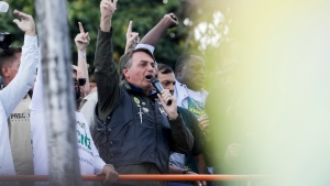 Brazil's President Jair Bolsonaro talks to supporters after joining a caravan of motorcycle enthusiasts through the streets of the city, organized to show support for Bolsonaro, in Sao Paulo, Brazil, Saturday, June 12, 2021. (AP Photo/Marcelo Chello)