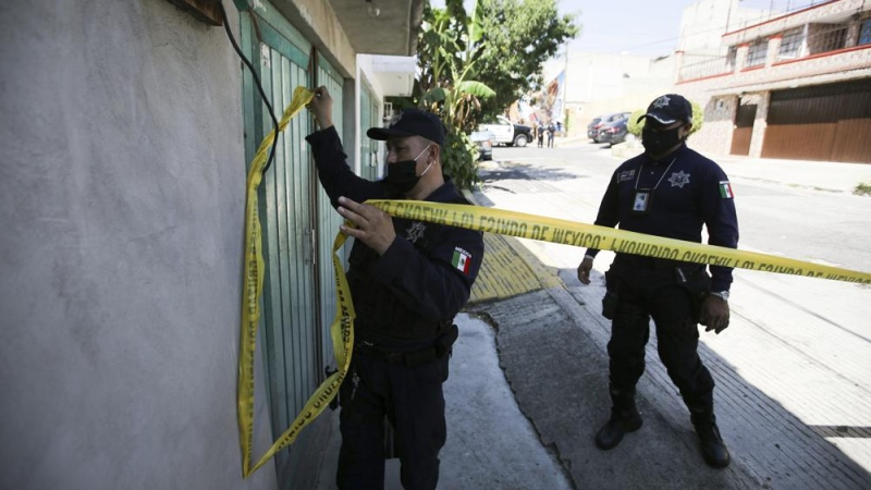 A police officer marks a security perimeter around the house where bones were found under the floor in the Atizapan municipality of the State of Mexico, Thursday, May 20, 2021. (AP Photo/Fernando Llano)