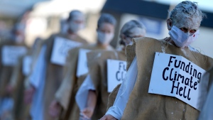 Climate protestors march in potato sacks with signs during a demonstration in Falmouth, Cornwall, England, Saturday, June 12, 2021. Leaders of the G7 gather for a second day of meetings on Saturday, in which they will discuss COVID-19, climate, foreign policy and the economy. (AP Photo/Alastair Grant)