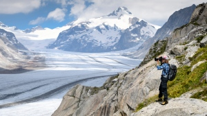 """In this July 21, 2020 file photo, Swiss photographer David Carlier takes photographs of the Swiss Aletsch glacier, the longest glacier in Europe, in Fieschertal, Switzerland. Swiss voters are casting ballots Sunday June 13, 2021, in a referendum on a proposed """"carbon dioxide law"""" that would hike fees and taxes on fuels that produce greenhouse gases, as their Alpine country experiences an outsized impact from the fallout of climate change.(Laurent Gillieron/Keystone via AP, File)"""