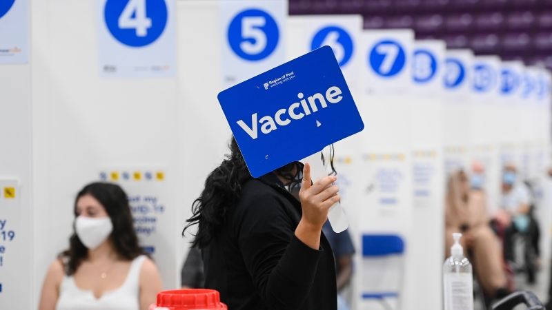 A health-care worker holds up a sign signaling she needs more COVID-19 vaccines at the 'hockey hub' mass vaccination facility at the CAA Centre during the COVID-19 pandemic in Brampton, Ont., on Friday, June 4, 2021.
