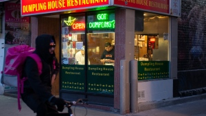 A food delivery courier cycles past a restaurant in Toronto's Chinatown, on Saturday March 21, 2020. THE CANADIAN PRESS/Chris Young