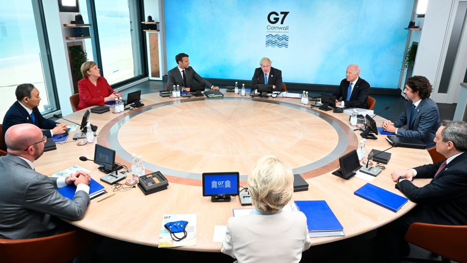Clockwise from top centre, British Prime Minister Boris Johnson, U.S. President Joe Biden, Prime Minister Justin Trudeau, Italian Prime Minister Mario Draghi, President of the European Commission Ursula von der Leyen, President of the European Council Charles Michel, Japanese Prime Minister Yoshihide Suga, German Chancellor Angela Merkel and French President Emmanuel Macron, sit around the table at the top of the G7 meeting in Carbis Bay, England on Friday, June 11, 2021. (Leon Neal/Pool Photo via AP)