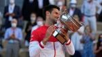 Serbia's Novak Djokovic holds the cup after defeating Stefanos Tsitsipas of Greece during their final match of the French Open tennis tournament at the Roland Garros stadium Sunday, June 13, 2021 in Paris. Djokovic won 6-7, 2-6, 6-3, 6-2, 6-4. (AP Photo/Michel Euler)