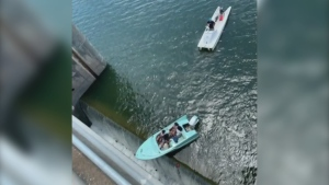Aerial of boat dangling precariously over dam