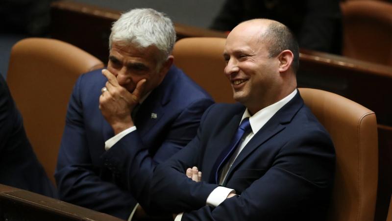 Israel's new prime minister Naftali Bennett sits with Yair Lapid, left, during a Knesset session in Jerusalem Sunday, June 13, 2021. (AP Photo/Ariel Schalit)