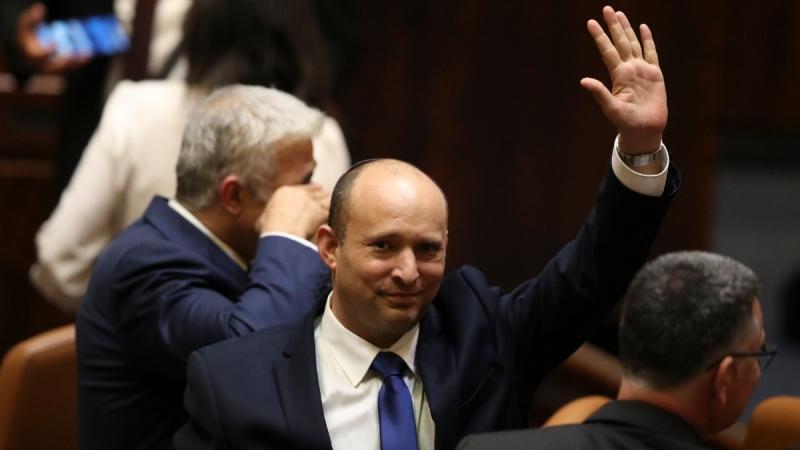 Israel's new prime minister Naftali Bennett raises his hand during a Knesset session in Jerusalem on June 13, 2021. (Ariel Schalit / AP)
