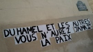 """In this Jan.19, 2021 file photo, signs on the wall reads """"Duhamel, and the others, you will never be in peace"""" referring to prominent French political expert Olivier Duhamel, in Paris. French prosecutors have dropped an investigation into incestuous sexual abuse of a 14-year-old by a prominent French political commentator, a case that unleashed an online movement against similar abuse. (AP Photo/Francois Mori, File)"""