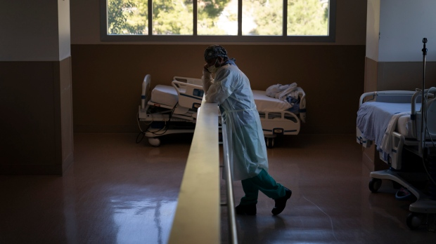 In this Nov. 19, 2020, file photo, respiratory therapist Babu Paramban talks on the phone next to hospital beds while taking a break in the COVID-19 unit at Providence Holy Cross Medical Center in the Mission Hills section of Los Angeles. (AP Photo/Jae C. Hong, File)