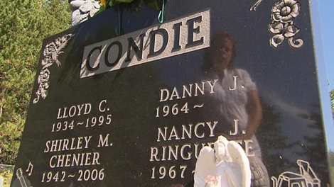 Shirley Condie, whose daughters is seen reflected in the tombstone, was thought to have been buried beside her husband, even though her family had been denied the open-casket that was requested. After an OPP investigation, her remains were found in another grave site.