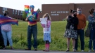 Aila Douglas, centre, holds a love sign alongside her father Mark in front of the East Wiltshire School in Cornwall, Prince Edward Island on Monday June 14, 2021. School board officials in P.E.I. are investigating reports that a recent Pride Day event at a junior high school was disrupted by some students who dressed in black and harassed classmates who said they supported the LGBTQ community. THE CANADIAN PRESS/John Morris