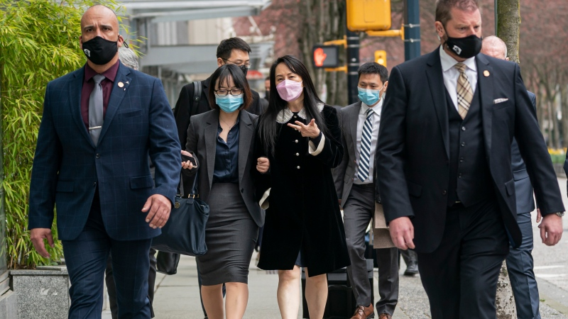 Meng Wanzhou, chief financial officer of Huawei, walk down the street with an acquaintance after leaving B.C. Supreme Court during a lunch break at her extradition hearing, in Vancouver, B.C., Thursday, April 1, 2021. THE CANADIAN PRESS/Rich Lam