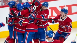 Montreal Canadiens right wing Tyler Toffoli (73) is mobbed by teammates after scoring the game-winning goal following overtime NHL Stanley Cup playoff hockey action against the Winnipeg Jets, in Montreal, Monday, June 7, 2021. THE CANADIAN PRESS/Ryan Remiorz