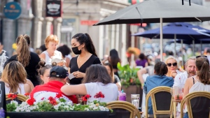 People sit on a terrace in Old Montreal, Sunday, June 13, 2021, as the COVID-19 pandemic continues in Canada and around the world. THE CANADIAN PRESS/Graham Hughes