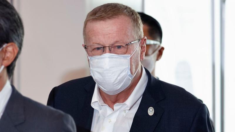 International Olympic Committee Vice President John Coates, centre, wearing a face mask, arrives at Haneda Airport in Tokyo Tuesday, June 15, 2021. (Takuto Kaneko/Kyodo News via AP)