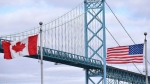 Canadian and American flags fly near the Ambassador Bridge at the Canada-U.S. border crossing in Windsor, Ont. on March 21, 2020. (Rob Gurdebeke / THE CANADIAN PRESS)