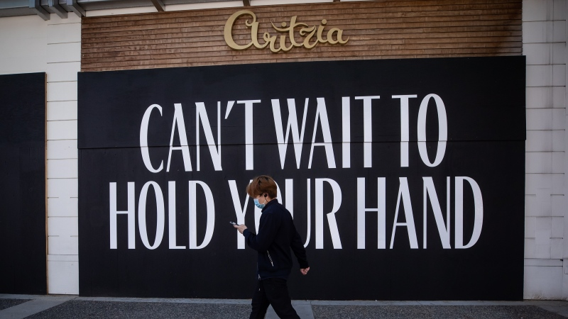 A message is painted on the boarded up windows of a closed Aritzia clothing store on Robson Street, in Vancouver, on Wednesday, May 6, 2020. THE CANADIAN PRESS/Darryl Dyck