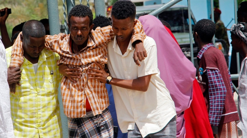 Somalis help a civilian who was wounded in suicide bomb attack at a military base in Mogadishu, Somalia,  June 15, 2021 (Farah Abdi Warsameh / AP)