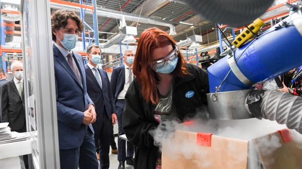 Canada's Prime Minister Justin Trudeau, second left, watches an employee use a dry ice packing machine during a working visit to the Pfizer pharmaceutical company in Puurs, Belgium, Tuesday, June 15, 2021. Canadian Prime Minister Justin Trudeau paid a visit to the Belgian Pfizer factory on Tuesday to thank employees making the COVID-19 vaccine. (Frederic Sierakowski, Pool via AP)