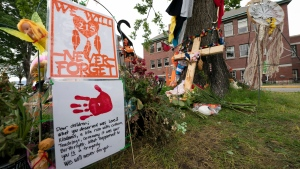 Signs are pictured at a memorial outside the Residential School in Kamloops, B.C., Saturday, June, 13, 2021. The remains of 215 children were discovered buried near the former Kamloops Indian Residential School earlier this month. THE CANADIAN PRESS/Jonathan Hayward
