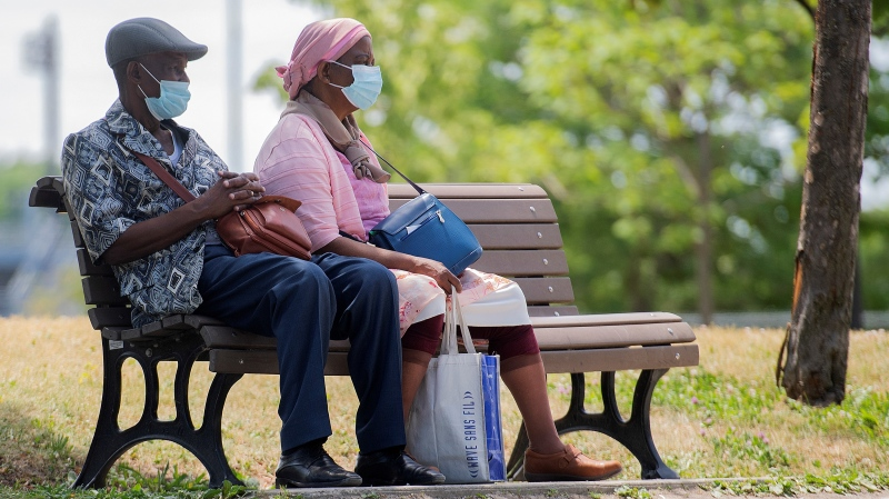 People wear face masks as they sit in a park in Montreal, Sunday, June 13, 2021, as the COVID-19 pandemic continues in Canada and around the world. THE CANADIAN PRESS/Graham Hughes
