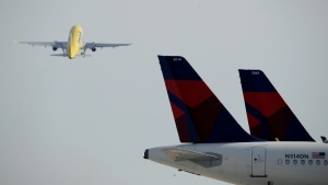 Parked Delta Air Lines jets are seen in the foreground at Kansas City International Airport, on April 1, 2020. (Charlie Riedel / AP)