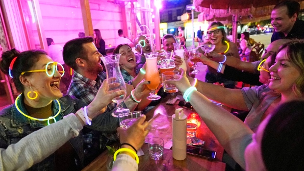 """Emily Baumgartner, left, and Luke Finley, second from left, join friends from their church group in a birthday toast to one of the members, upper right, during their weekly """"Monday Night Hang"""" gathering at the Tiki Bar on Manhattan's Upper West Side Monday, May 17, 2021, in New York. (AP Photo/Kathy Willens)"""