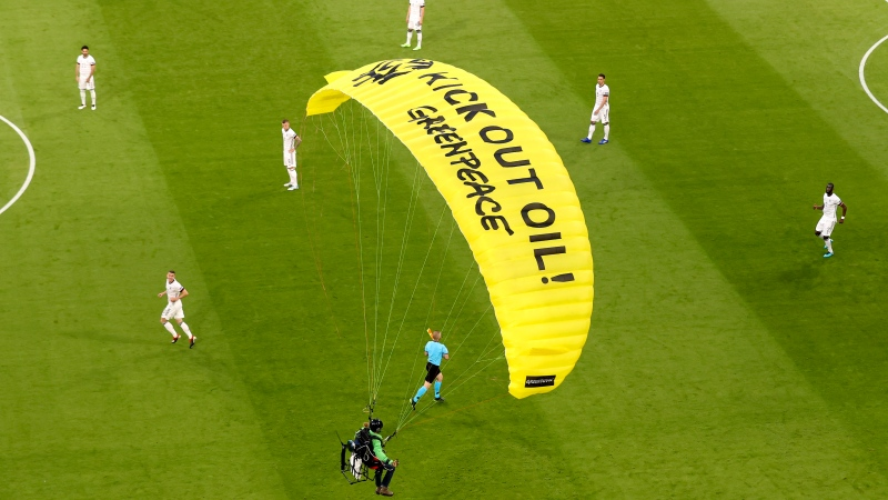 The German players look on as a Greenpeace paraglider lands in the stadium prior to the Euro 2020 soccer championship group F match between France and Germany at the Allianz Arena stadium in Munich, Tuesday, June 15, 2021. (AP Photo/ctivist Alexander Hassenstein, Pool)