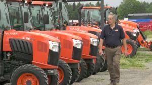 Laird Weagant walking by the few new tractors he has in stock. (Nate Vandermeer / CTV News Ottawa)