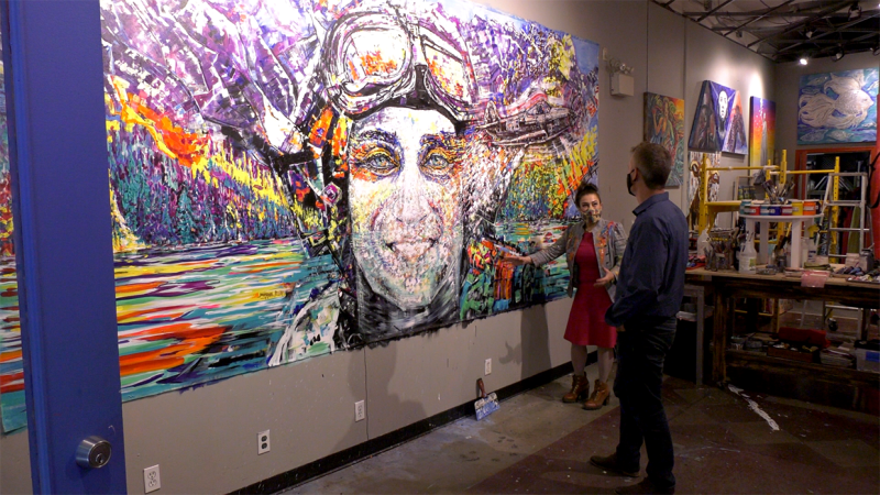 Artist Bany Declair shows some of the details of her painting she's donating to the Hangar Flight Museum to its executive director Brian Desjardins