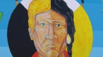 The focal point of the mural is a two-faced man, half European and half Indigenous symbolizing cooperation. (Francois Biber/CTV Saskatoon)