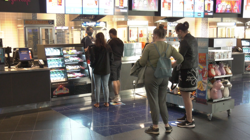 Theatre patrons stand in line at the snack counter at Cineplex Marine Gateway in Vancouver, B.C., on June 15, 2021.