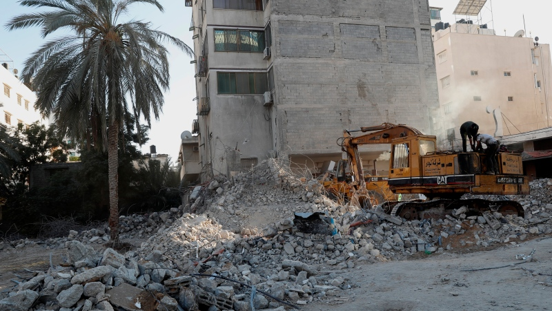 Workers remove the rubble of a building destroyed by an airstrike in Gaza City, Tuesday, June 15, 2021. (AP Photo/Adel Hana)