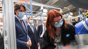 Prime Minister Justin Trudeau, second left, watches an employee use a dry ice packing machine during a working visit to the Pfizer pharmaceutical company in Puurs, Belgium, Tuesday, June 15, 2021. (Frederic Sierakowski, Pool via AP)