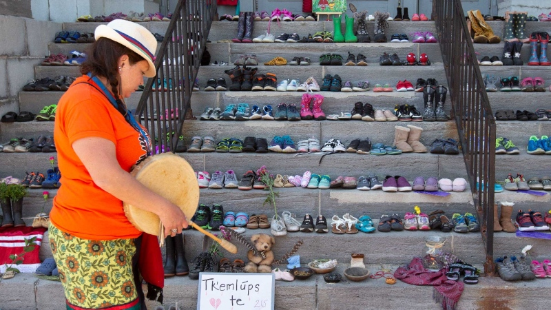 A person look at all the shoes outside City hall in Kingston, Ont., on Monday, May 31, 2021. The remains of 215 children were recently discovered on the grounds of the former Kamloops Indian Residential School. THE CANADIAN PRESS/Lars Hagberg