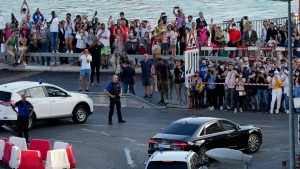 Spectators watch the arrival of a motorcade with Russian Foreign Minister Sergey Lavrov in Geneva, Switzerland Tuesday, June 15, 2021. (AP Photo/Markus Schreiber)