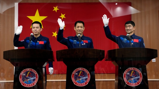 Chinese astronauts, from left, Tang Hongbo, Nie Haisheng, and Liu Boming wave during a press conference at the Jiuquan Satellite Launch Center ahead of the Shenzhou-12 launch from Jiuquan in northwestern China, Wednesday, June 16, 2021. (AP Photo/Ng Han Guan)