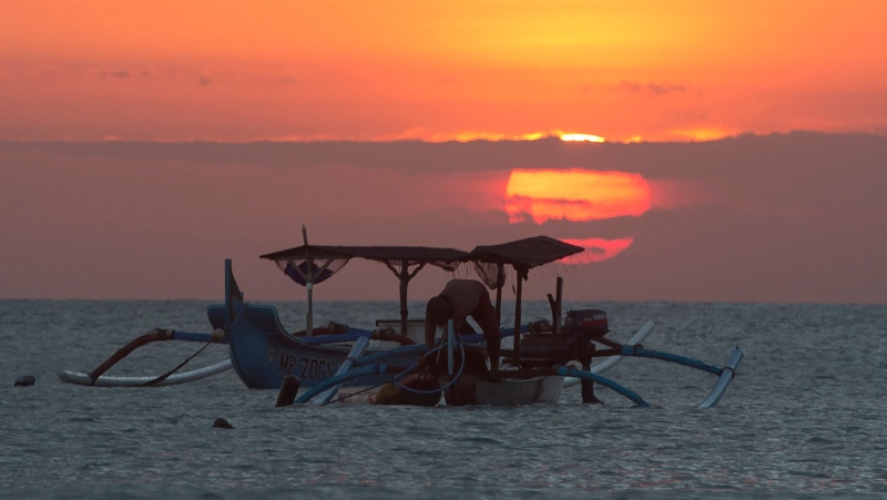 A fisherman works in his traditional boat at Kuta beach during the sunset in Bali, Indonesia, Wednesday, May 12, 2021. (AP Photo/Firdia Lisnawati)
