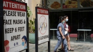 Customers wear face masks in an outdoor mall with closed business amid the COVID-19 pandemic in Los Angeles Friday, June 11, 2021. (AP Photo/Damian Dovarganes)