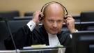 Karim Khan adjust his headphones in court in The Hague, the Netherlands, on June 4, 2007. (Robert Vos / AP)