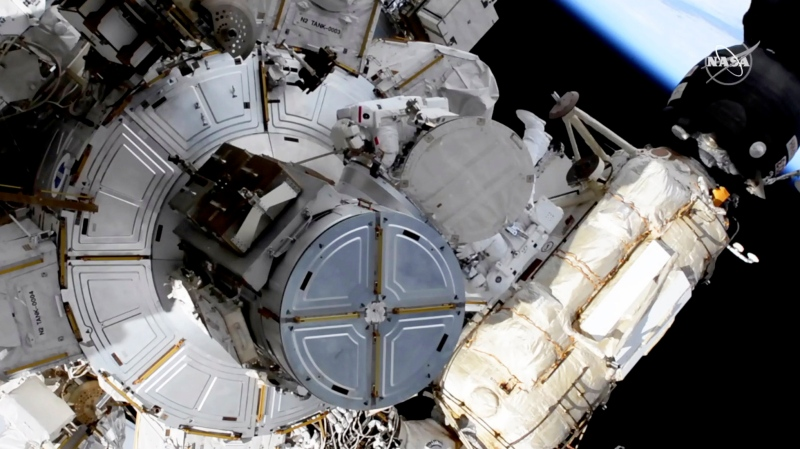 In this image taken from NASA video, French astronaut Thomas Pesquet, top center, and NASA astronaut Shane Kimbrough venture out on a spacewalk Wednesday, June 16, 2021, to outfit the International Space Station with powerful, new solar panels to handle the growing electrical demands from upcoming visitors. (NASA via AP)