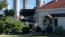 An employee walks towards a historic farm house located just in front of a fire-damaged portion of the Coldstream Concrete facility in Middlesex County, Ont. on Wednesday, June 16, 2021. (Sean Irvine / CTV News)
