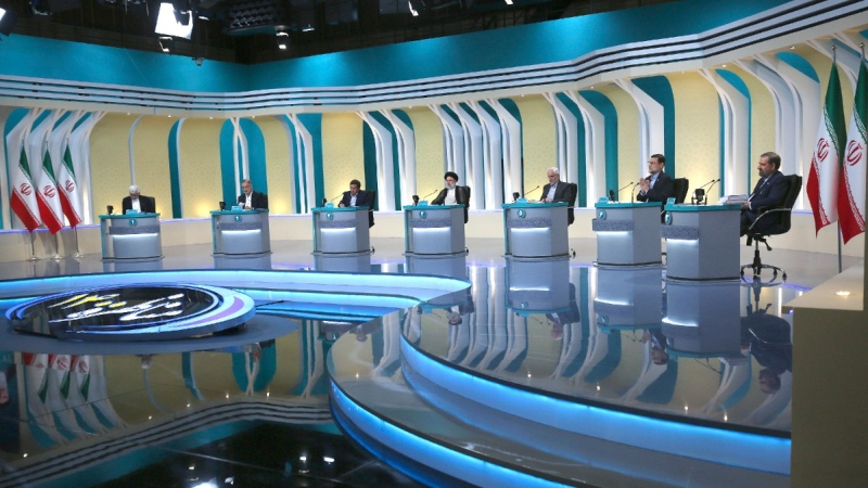 In this picture made available by Young Journalists Club, YJC, presidential candidates for June 18, elections from left to right, Saeed Jalili, Alireza Zakani, Abdolnasser Hemmati, Ebrahim Raisi, Mohsen Mehralizadeh, Amir Hossein Ghazizadeh Hashemi and Mohsen Rezaei attend the final debate of the candidates while Ebrahim Raisi listens at a state-run TV studio in Tehran, Iran, on June 12, 2021. (Morteza Fakhri Nezhad / Young Journalists Club, YJC via AP)