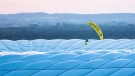 A man in a Greenpeace paraglider flies into the stadium prior to the Euro 2020 soccer championship group F match between France and Germany at the Allianz Arena stadium in Munich, Tuesday, June 15, 2021. (Matthias Balk/DPA via AP)