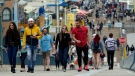 In this May 13, 2021, file photo, visitors walk without masks on the pier in Santa Monica, Calif. (AP Photo/Marcio Jose Sanchez, File)