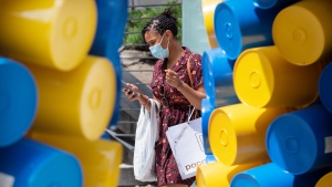 A woman wears a face mask as she walks by an art installation in Montreal, Sunday, June 13, 2021, as the COVID-19 pandemic continues in Canada and around the world. THE CANADIAN PRESS/Graham Hughes